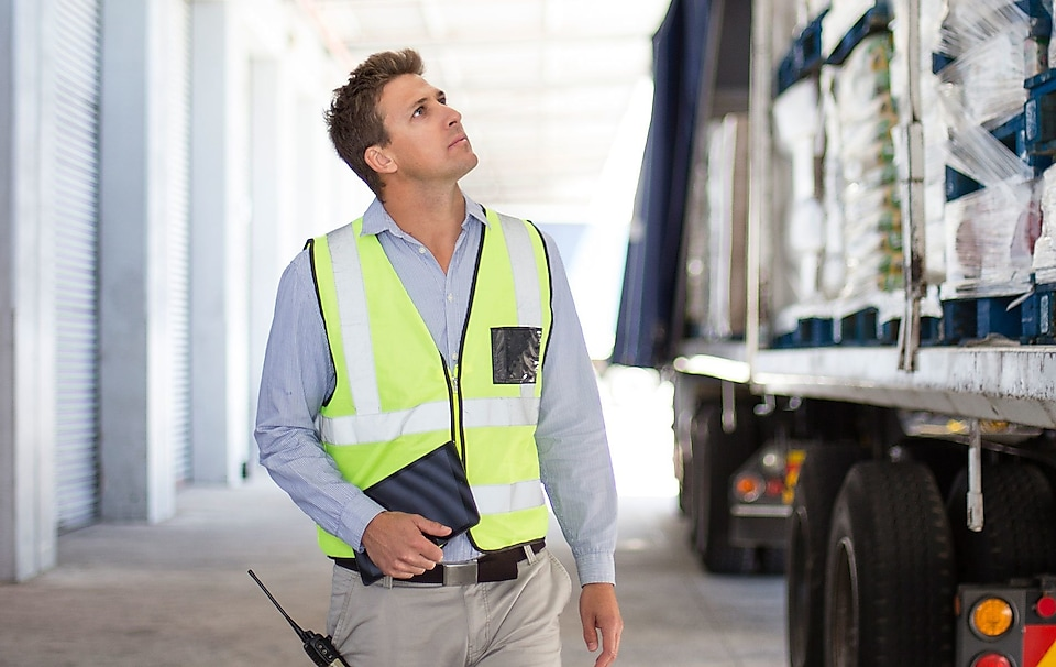 A man is looking at a truck's freight wearing a yellow safety vest.