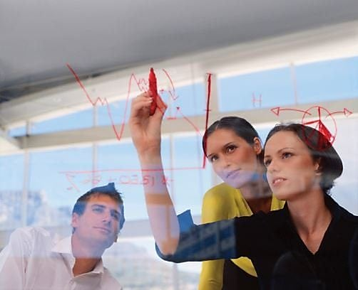 Women and a man drawing a chart on a glass wall